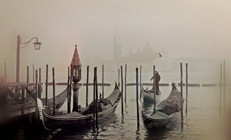 Gondolas in a canal on a foggy day